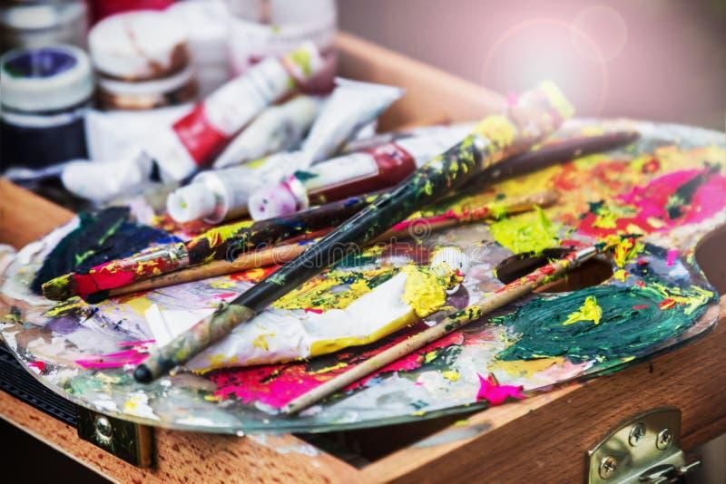 Het kunstenaars` s palet met verven en borstels stock fotografie