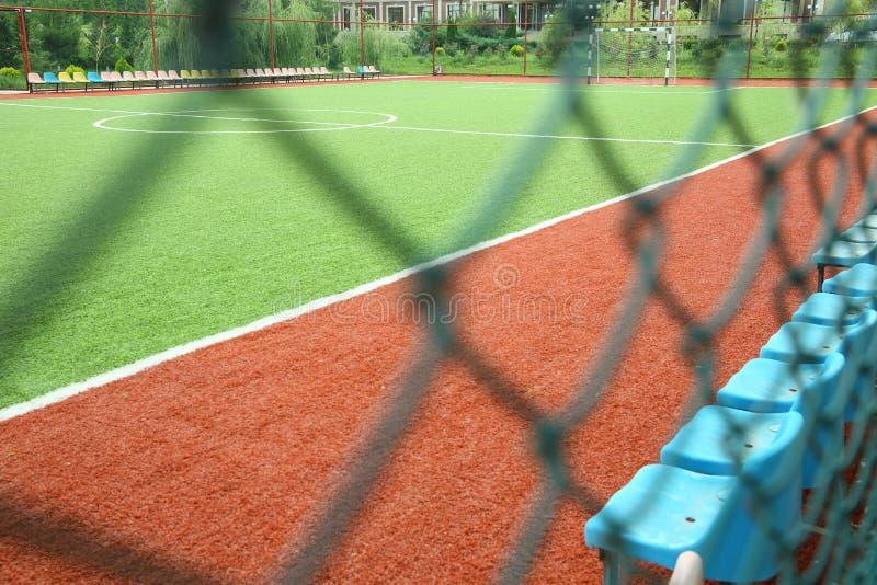 Het Kunstmatige Gras van Mini Football Goal On An Voetbaldoel op een groen gazon Voetbalgebied dichtbij omheining bij dag zonnige stock foto's