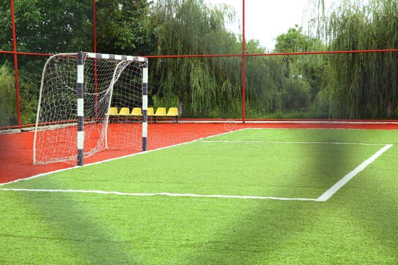 Het Kunstmatige Gras van Mini Football Goal On An Voetbaldoel op een groen gazon Voetbalgebied dichtbij omheining bij dag zonnige stock afbeelding