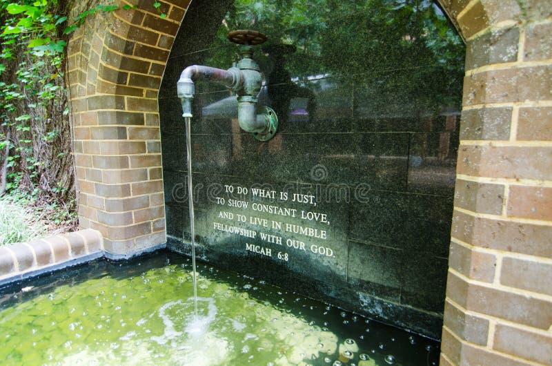 Het kunstwerk van de waterkraan met het woord in heilige bijbel ` om te doen wat enkel constante liefde moet tonen en in bescheid stock foto's