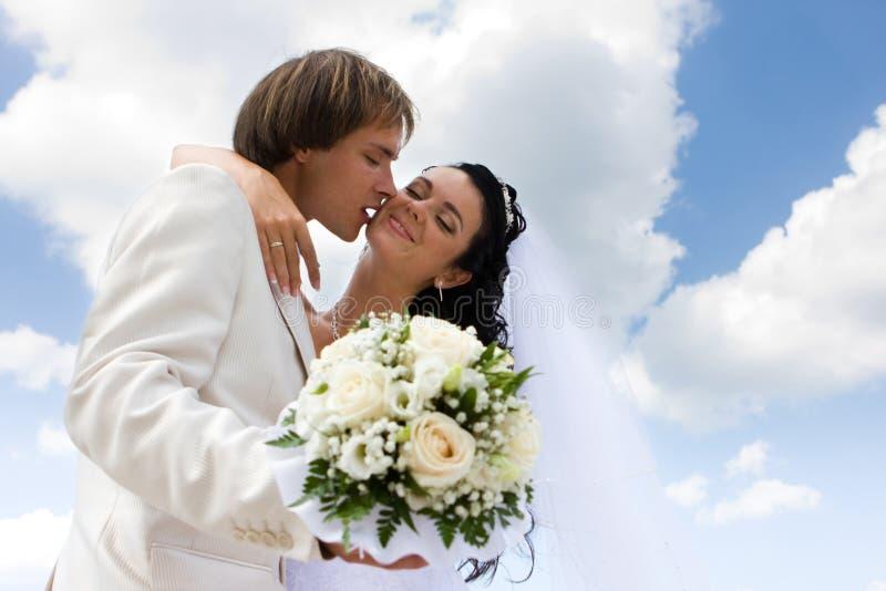Het kussen van de bruid en van de bruidegom royalty-vrije stock afbeeldingen