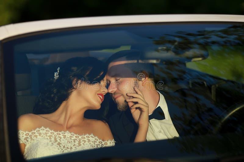 Het kussen van de bruid en van de bruidegom in de auto stock afbeelding