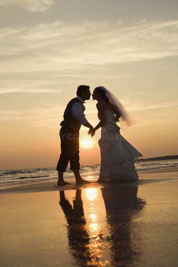 Het kussen van de bruid en van de bruidegom op strand. royalty-vrije stock foto
