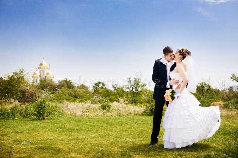 Het kussen van de bruid in het park stock fotografie