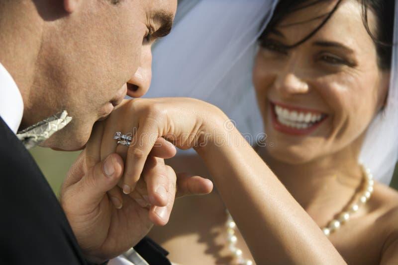 Het kussen van de bruidegom de hand van de bruid royalty-vrije stock afbeeldingen