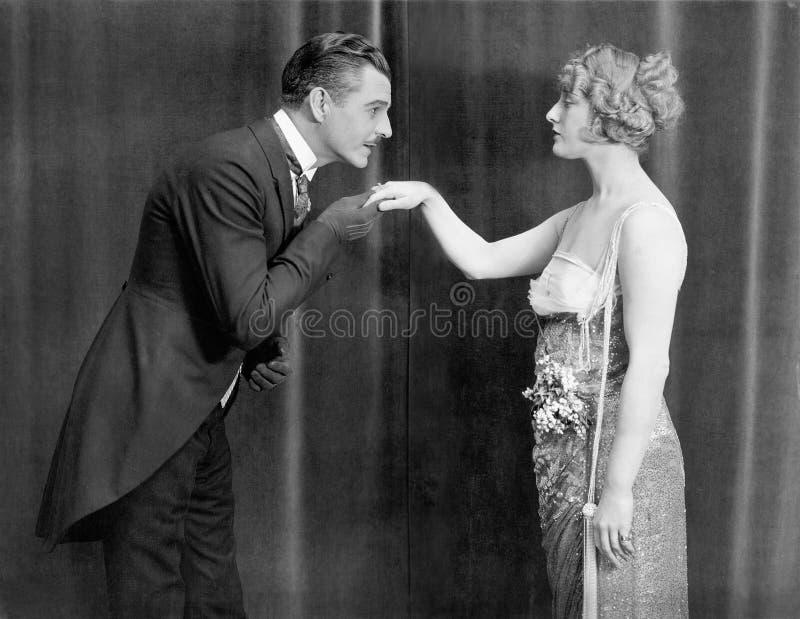 Het kussen van de mens womans hand stock fotografie