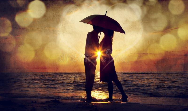 Het kussen van het paar onder paraplu bij het strand in zonsondergang. Foto in o stock foto