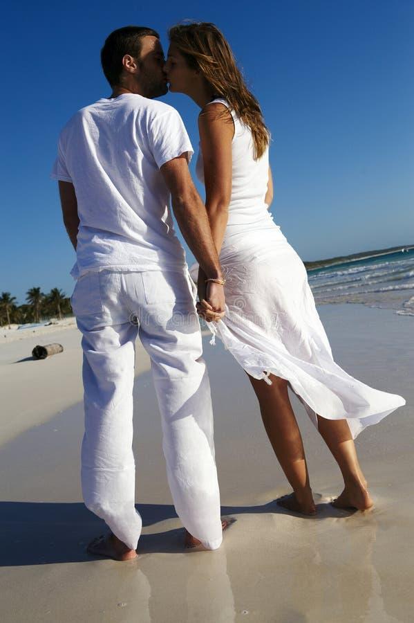 Het kussen van het paar op strand stock fotografie