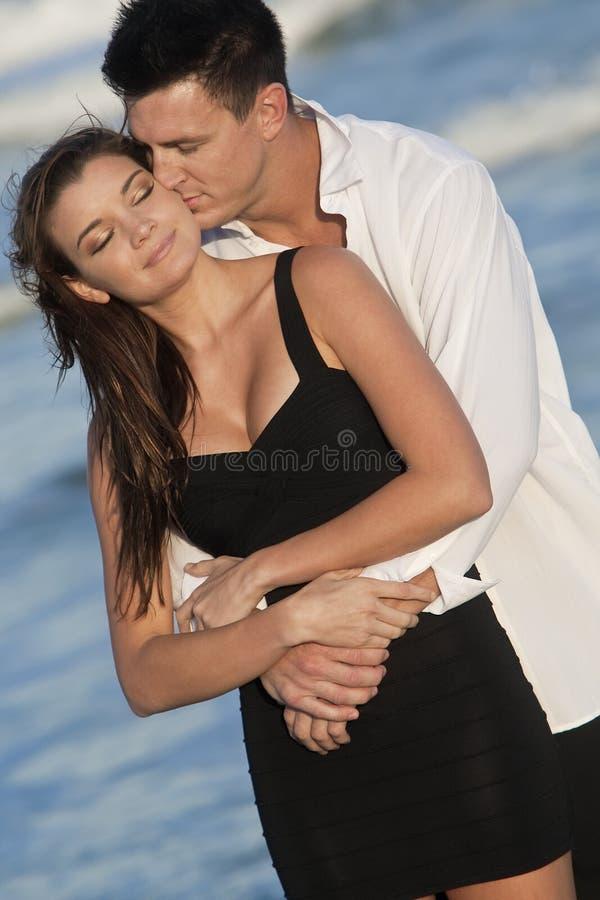 Het Kussen van het paar in Romantische Greep op Strand stock afbeelding