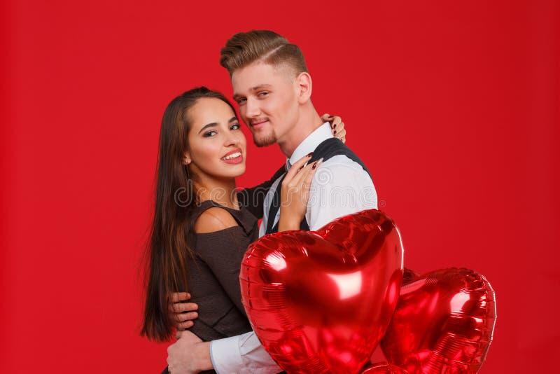 Het kussen van jong paar met rode luchtballons in een hartvorm op een rode achtergrond Het concept de Dag van Valentine ` s stock foto's