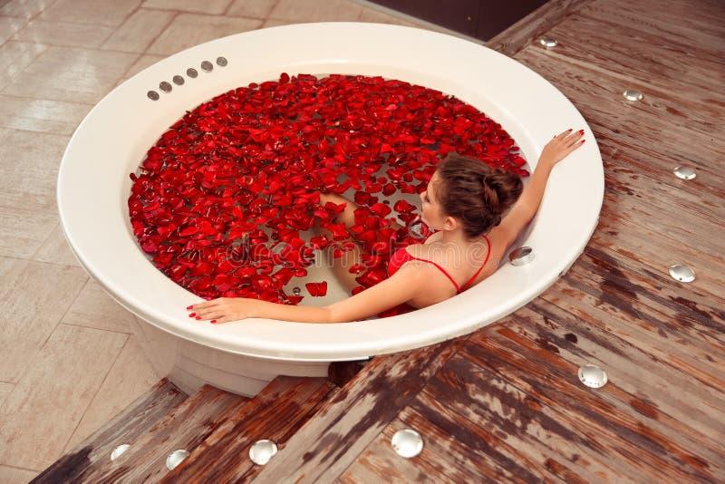 Het kuuroord ontspant Mooi meisje in Jacuzzi Bikinivrouw die in rond bad met rode roze bloemblaadjes liggen Gezondheid en schoonh stock fotografie