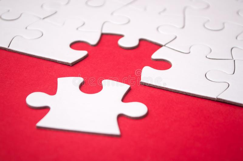 Het laatste stuk van puzzel het missen op rode achtergrond om de opdracht te voltooien stock afbeeldingen