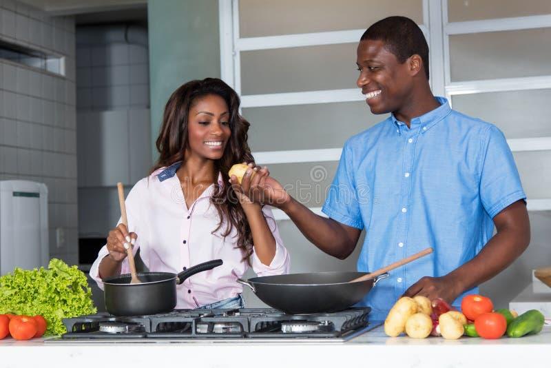 Het lachen het Afrikaanse Amerikaanse liefdepaar koken bij keuken royalty-vrije stock afbeeldingen