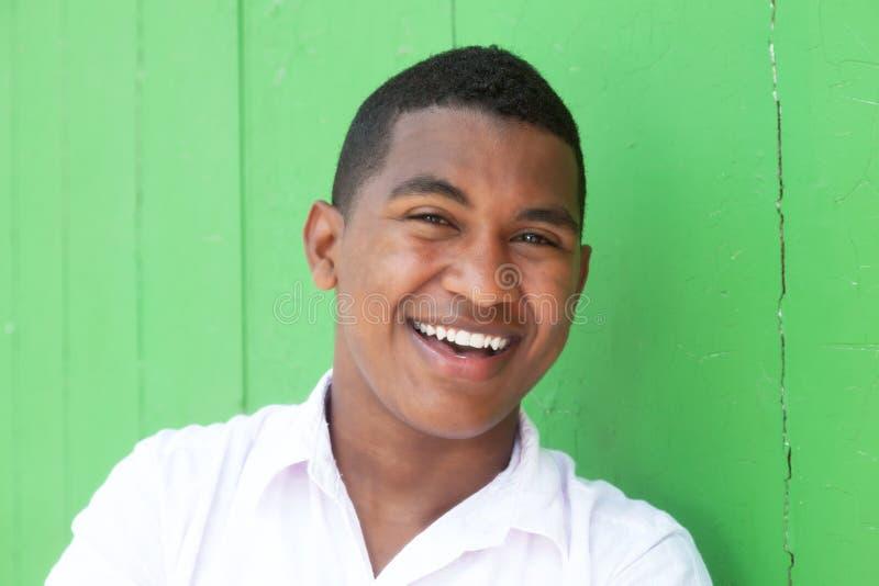 Het lachen Caraïbische kerel voor een groene muur stock afbeelding