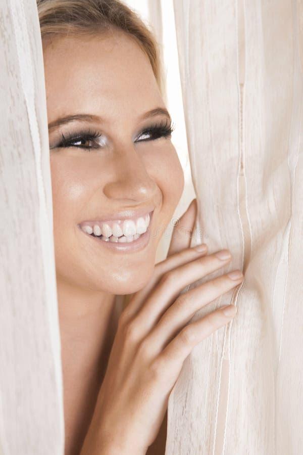 Het lachen de close-up van het blondemeisje onder venstergordijn dicht omhoog stock fotografie
