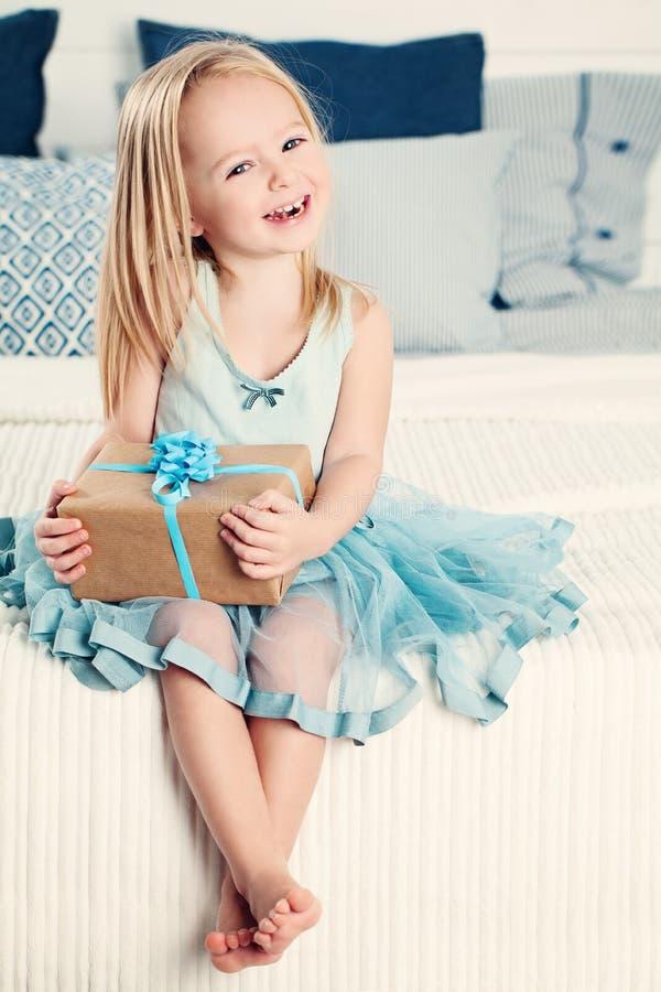 Het lachen de Holdingsgift van het Kindmeisje thuis stock fotografie