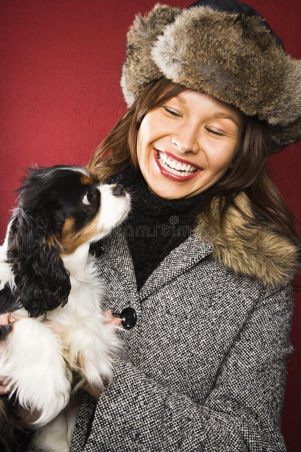 Het lachen de hond van de vrouwenholding. stock foto's