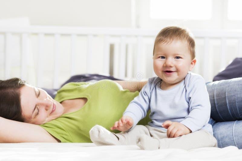 Het lachen de zitting van de babyjongen in bed samen met zijn moeder. royalty-vrije stock afbeeldingen