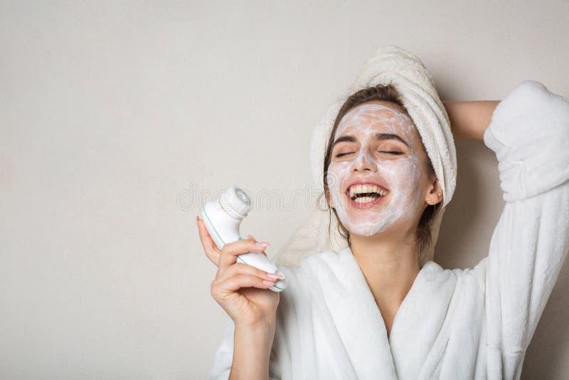 Het lachen het donkerbruine meisje stellen met bevochtigende roommasker en gezichtsreinigingsmachine Lege ruimte royalty-vrije stock afbeelding