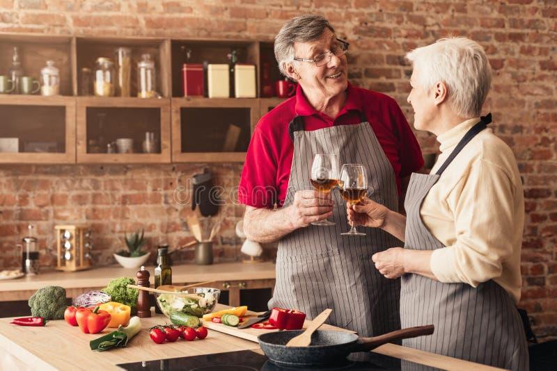 Het lachen hartelijke teruggetrokken paar het drinken wijn samen in keuken stock fotografie
