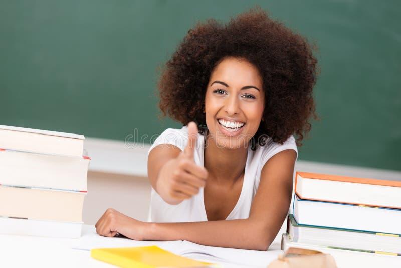 Het lachen het jonge student geven duimen omhoog stock foto