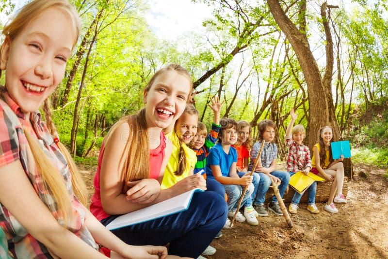 Het lachen jonge geitjes die op login het de zomerkamp zitten royalty-vrije stock afbeelding