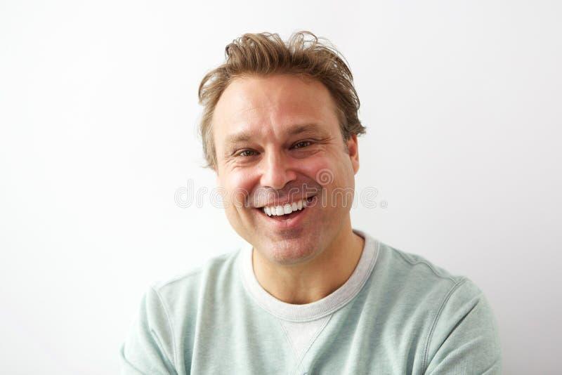 Het lachen jonge kerel die zich tegen witte muur bevinden royalty-vrije stock foto