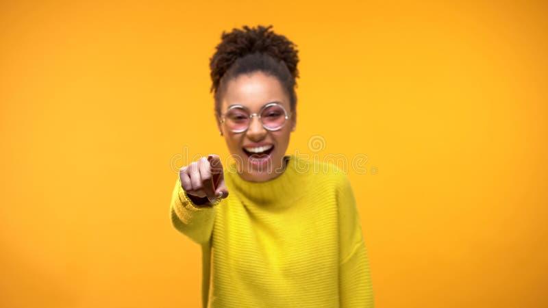 Het lachen jonge vrouwelijke het richten vinger in camera, hebbend pret, het gekscheren, positiviteit stock foto's