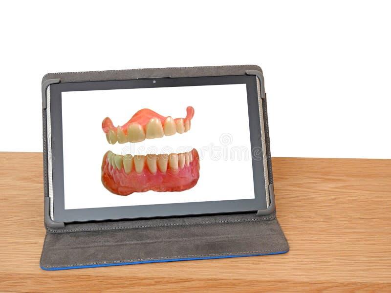 Het lachen kunstgebitsgebitten op het scherm van de tabletcomputer stock foto