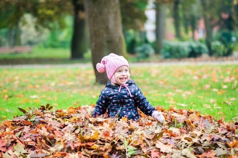 Het lachen meisje het spelen in het de herfstpark royalty-vrije stock afbeelding