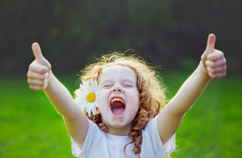 Het lachen meisje het tonen beduimelt omhoog royalty-vrije stock afbeeldingen