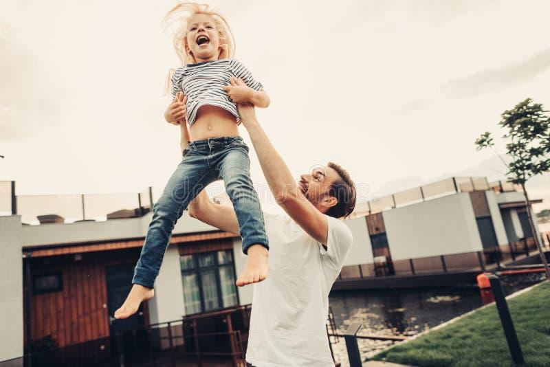 Het lachen papa het spelen met blije buiten dochter royalty-vrije stock afbeelding