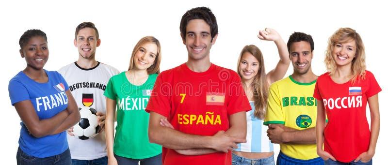 Het lachen Spaanse voetbalventilator met het toejuichen van groep andere ventilators stock afbeelding