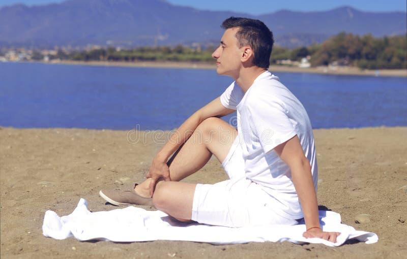 Het lachen strandkerel in wit borrels en overhemd De ondernemer geniet van blijvend op het strand Mens op strand die in zand ligg stock afbeelding