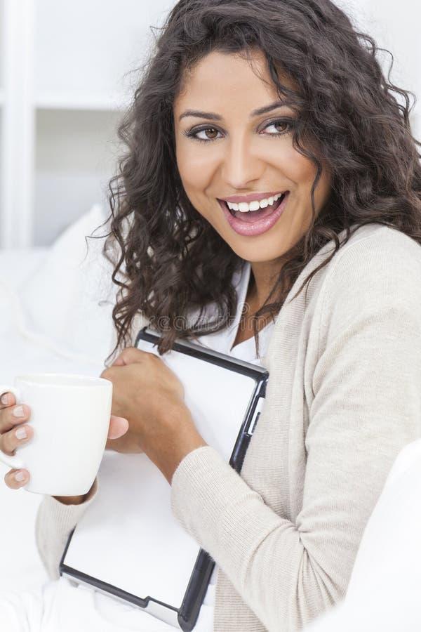 Het Lachen van de vrouw het Drinken van de Computer van de Tablet Koffie stock foto's