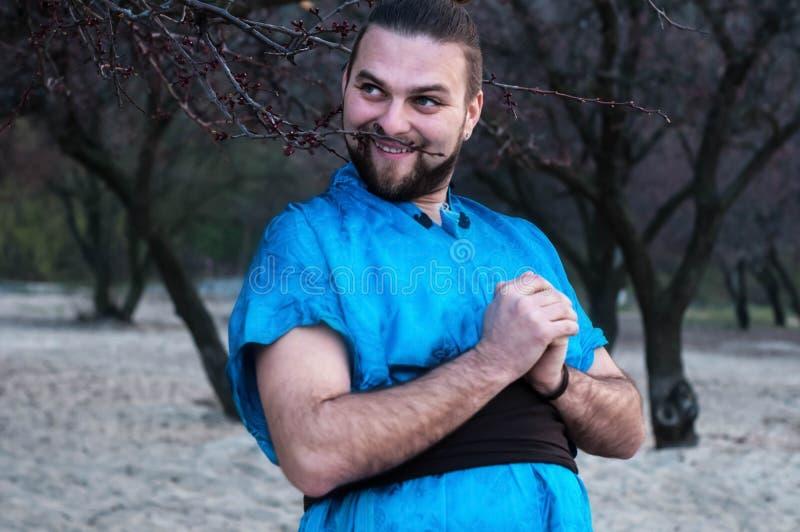 Het lachen het voor de gek houden rond de knappe gebaarde mens in blauwe kimono die bevindt zich met clasped handen stock fotografie