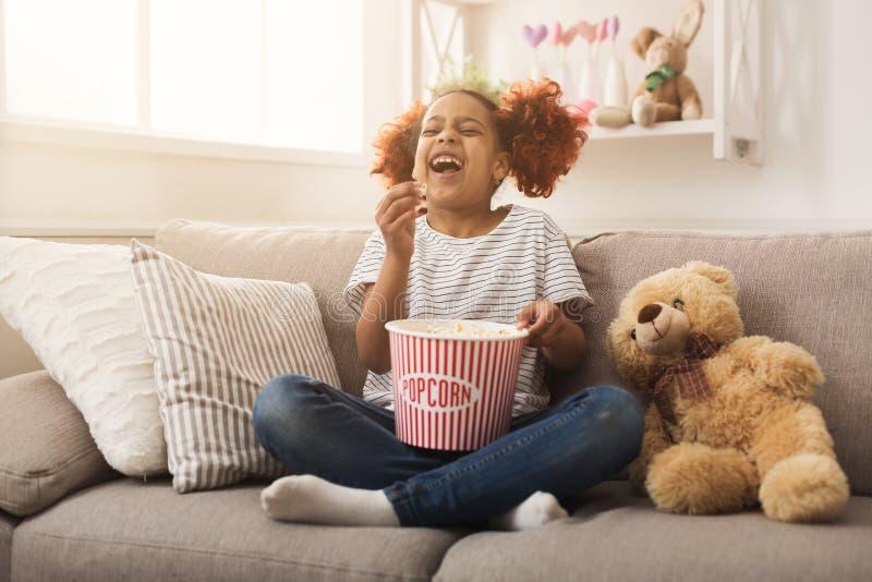 Het lachen zwarte meisje het letten op film thuis stock fotografie