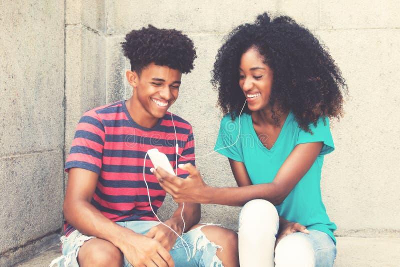 Het lachende Afrikaanse Amerikaanse jonge volwassen paar houdt van muziek royalty-vrije stock foto