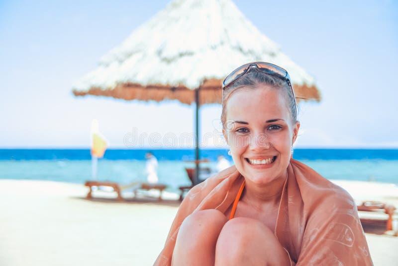 Het lachende en gelukkige meisje in een oranje zwempak zit op het strand en geniet van de golven, achter haar en helder royalty-vrije stock foto's