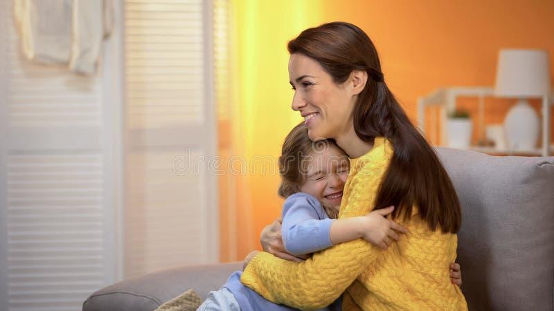 Het lachende mamma en dochter omhelzen, verhouding van liefde en vertrouwen, kinderjaren royalty-vrije stock afbeelding