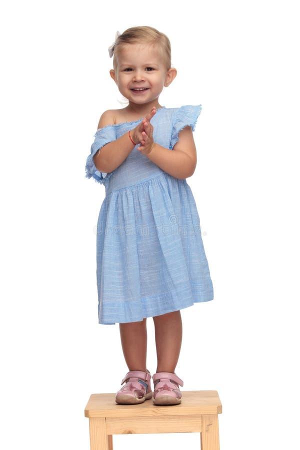Het lachende meisje in blauwe kleding slaat haar handen stock foto
