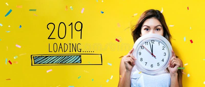 Het laden nieuw jaar 2019 met jonge vrouw die een klok houden stock fotografie