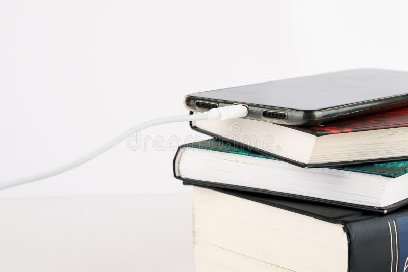 Het laden smartphone op hoop van boeken op een witte achtergrond royalty-vrije stock fotografie