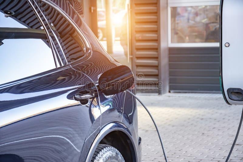 Het laden van een elektrische auto bij een de dienstgarage van de autoreparatiewerkplaats Het bijtanken voor elektrische auto's e stock afbeeldingen