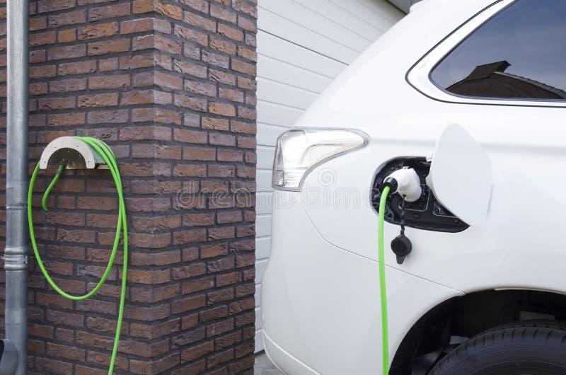 Het laden van een elektrische auto thuis stock afbeeldingen