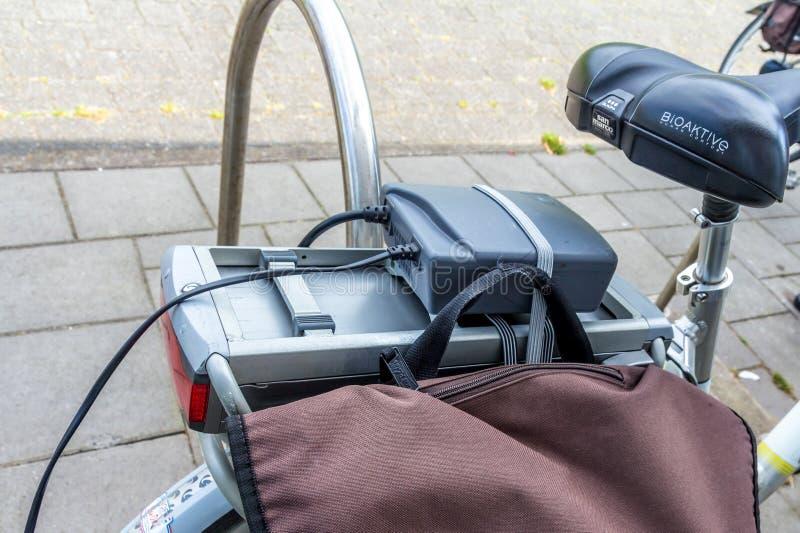 Het laden van een elektrische fietsbatterij stock fotografie