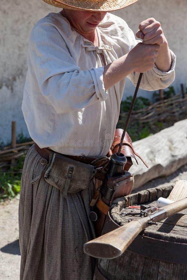 Het laden van een poeder aan het vat van een antiek jachtgeweer stock afbeeldingen