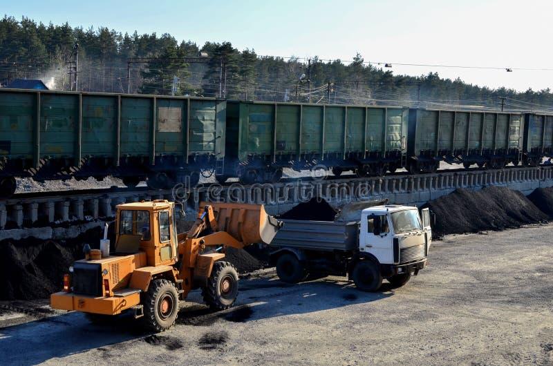 Het ladergraafwerktuig laadt steenkool in een stortplaatsvrachtwagen bij een ladingsstation stock foto's