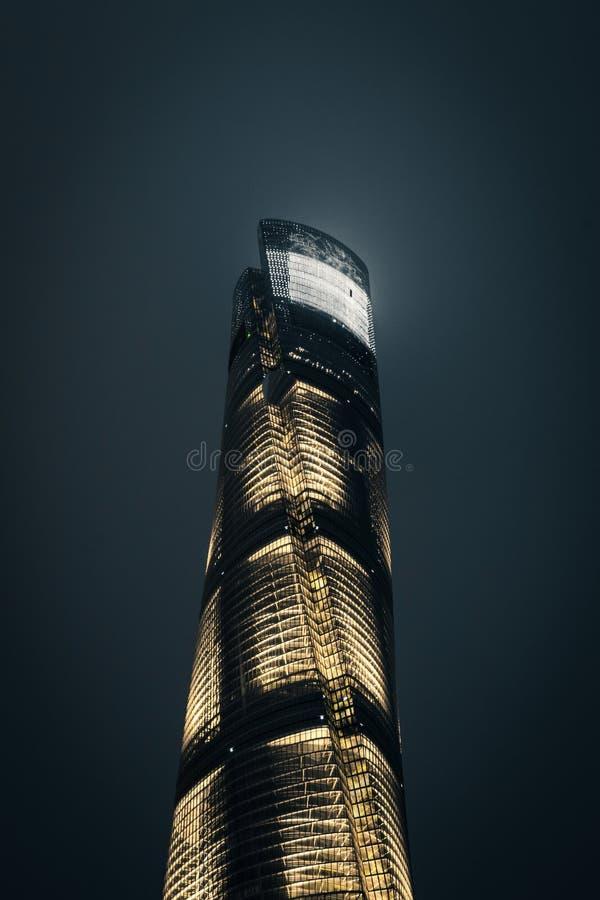 Het lage hoekschot van een lang spiraalvormig gebouw stak goed bij nacht met een donkere achtergrond aan stock foto's