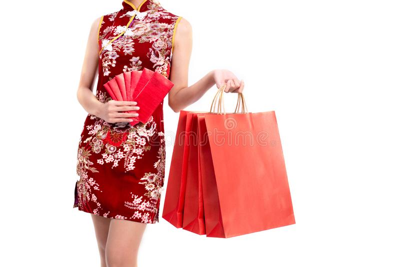 Het lagere lichaam van het Aziatische schoonheidsvrouw dragen cheongsam en draagt rood pakket van geld en het winkelen zak in Chi royalty-vrije stock fotografie